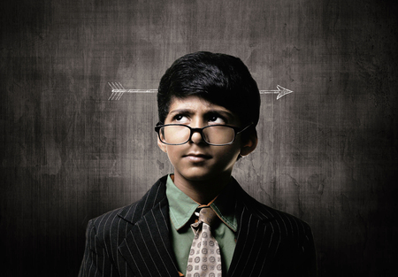 Cute Intelligent Little Boy Wearing Glasses On Nose, Thinking While Standing Before A Chalkboard,