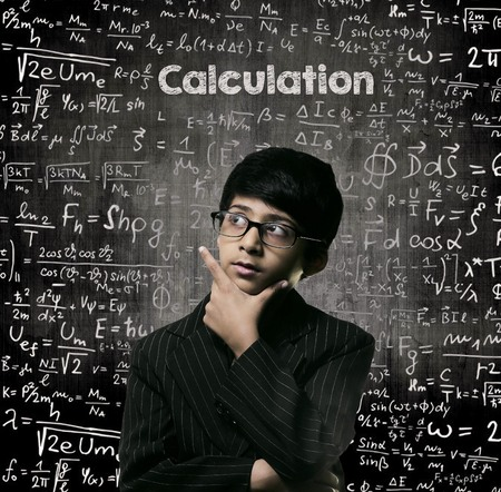 Cute Intelligent Little Boy Looking Up Thinking andWearing Glasses Standing Before A Chalkboard, Chemical Formulas Are Written On Board With The Chalkboard Typography Of The Word CALCULATION Imagens