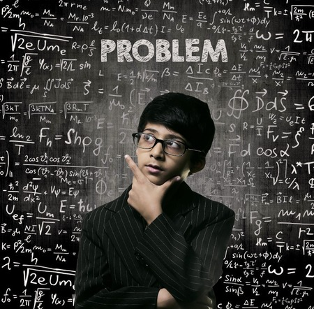 Cute Intelligent Little Boy Looking Up Thinking andWearing Glasses Standing Before A Chalkboard, Chemical Formulas Are Written On Board With The Chalkboard Typography Of The Word PROBLEM