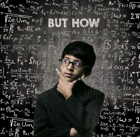 Cute Intelligent Little Boy Looking Up Thinking andWearing Glasses Standing Before A Chalkboard, Chemical Formulas Are Written On Board With The Chalkboard Typography Of The Words BUT HOW