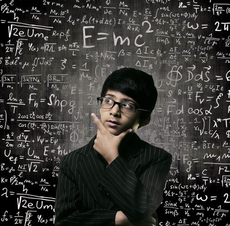 Cute Intelligent Little Boy Looking Up Thinking andWearing Glasses Standing Before A Chalkboard, Chemical Formulas Are Written On Board