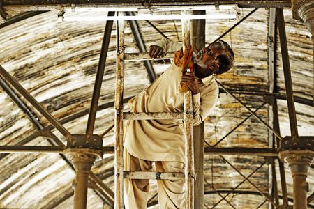 ethnology: Electrician reparing tube light at railway station at Hayderabad railway station, Pakistan 22-11-2014 Editorial