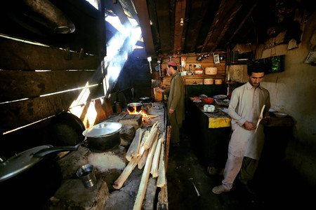 ethnology: Two tribes man cooking in the kitchen in mahodant lake, swat valley, Pakistan 15--10-2015