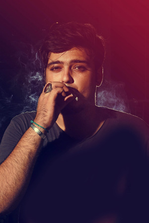 looking into camera: Young man smoking cigarette on dark background looking into camera wearing t shirt
