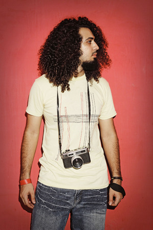 fashion photos: Closeup of one handsome passionate expressive cool young brunette photographer men with long curly hair holding a vintage SLR camera standing against red background Stock Photo