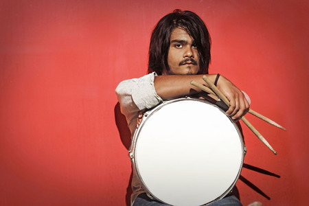 accoustic: young drummer holding sticks and snare isolated on red background looking into the camera Stock Photo