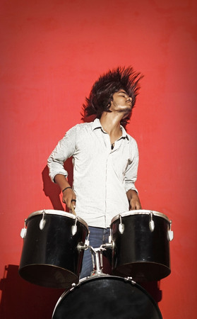 drummer: young drummer head banging isolated on red background