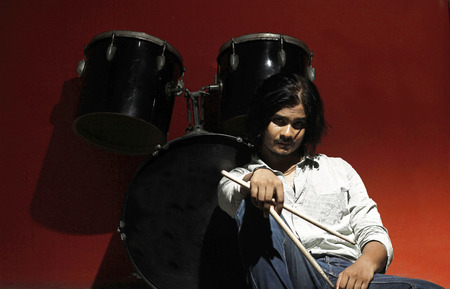 accoustic: young drummer holding sticks and sitting next to drum kit in spot light on red background looking into the camera