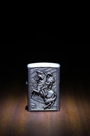 habbit:  Lighter on a wooden floor in the dark