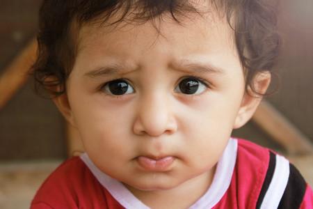 Close-up portret headshot verdacht, voorzichtiger kind jongen kijkt naar de camera. ongeloof, geïsoleerde scepsis grijze muur achtergrond. Stockfoto