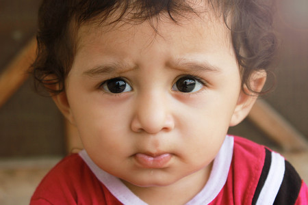 skepticism: Closeup up portrait headshot suspicious, cautious child boy looking at the camera. disbelief, skepticism isolated grey wall background. Stock Photo
