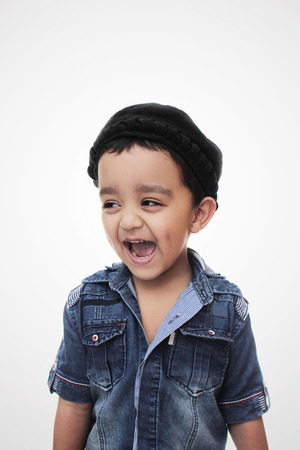 Portrait. happy little south asian boy wearing cultural hat. smiling and looking away from camera isolated on white Stock Photo