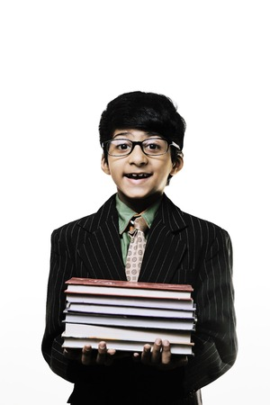 Cute Intelligent Little Boy Holding Books And Wearing Glasses, Smiling While isolated on white background