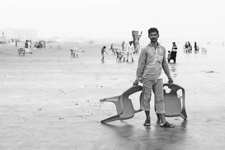Man standing on beach holding chairs at Clifton, Karachi, Pakistan 29062012