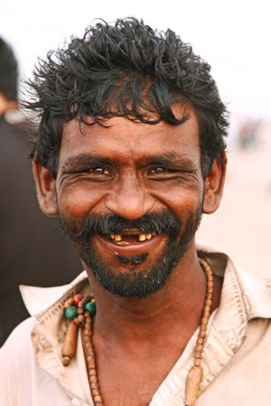 Portrait of a happy man smiling and looking at camera at Clifton beach, Karachi, Pakistan 26062012 Editorial