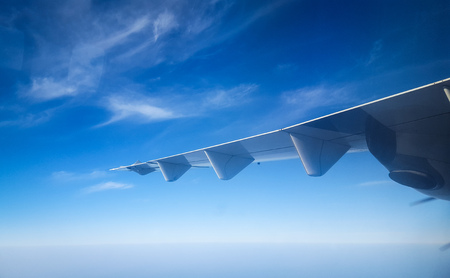 Plane wing against the beautiful blue sky and clouds and ocean from the window of plane Foto de archivo - 121490948