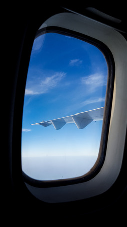 Plane wing against the beautiful blue sky and clouds and ocean from the window of plane - From inside the plane Foto de archivo - 121490950