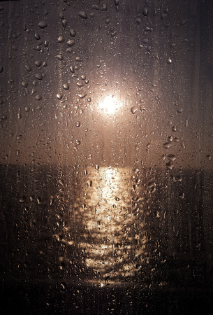 Water drops on the glass window against the beautiful sunset in the sea Foto de archivo - 121490970