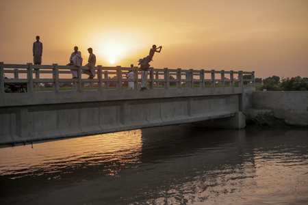Kids Sitting Water From A Bridge During Sunset, In Moro, Sindh, Pakistan 26/08/2017 Foto de archivo - 121483093