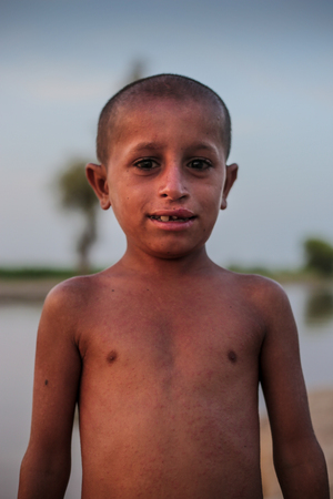 Portrait Of A Nacked Village Boy, Smiling And Looking At Camera In Sindh, Moro, Pakistan 26/08/2017 Foto de archivo - 121483097