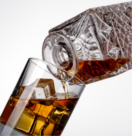snifter: whiskey is poured into a glass Stock Photo