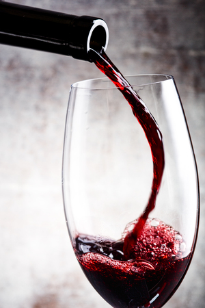 Pouring red wine into the glass against a wooden background Stock Photo