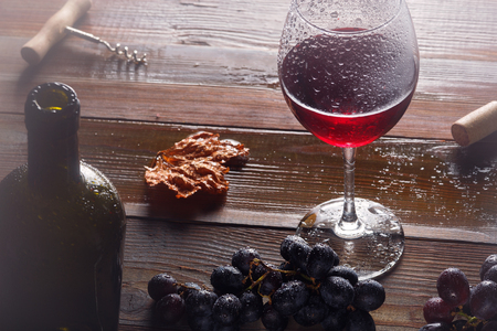 red wine and grapes. Wine and grapes in vintage setting with corks on wooden table