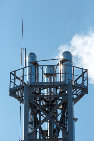 Chimneys of a Thermal Electric Plant on Blue Sky Background. Threat to the environment