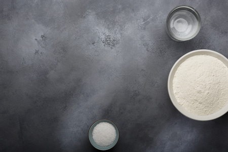 Risen or proved yeast dough for bread or pizza on a floured slate surface. Top view