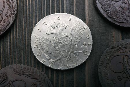 Numismatics. Old collectible coins made of silver and copper on a old wooden table. Top view.