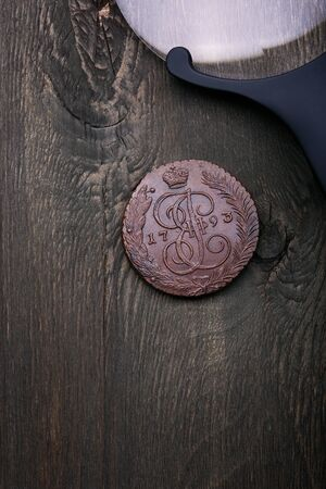 Numismatics. Old collectible coins made of copper on a old wooden table. Top view.