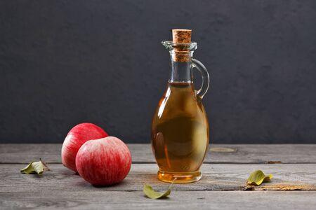 Manzanas maduras frescas y vinagre de sidra de manzana en una vieja mesa de madera. Fondo oscuro.