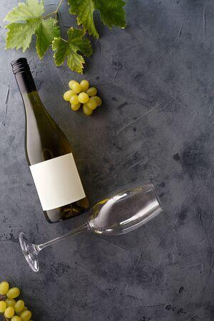Bottle of white wine with label. Glass of wine and grape. Wine bottle mockup. Top view. Foto de archivo - 134769638
