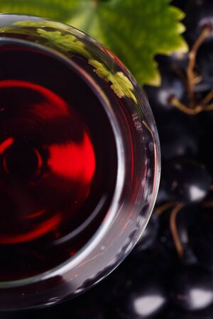 Red wine in a glass and grapes on the table. Dark background. Top view.