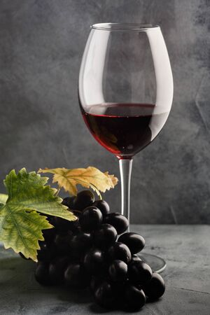 Red wine in a glass and grapes on the table. Dark background.