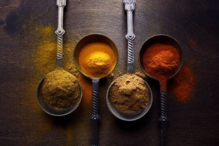 Wooden table of colorful spices. Top view. Dark background.
