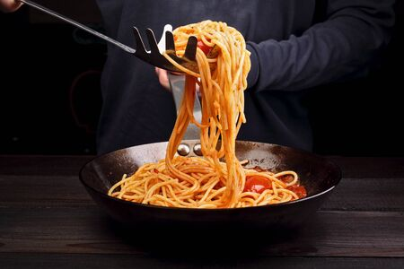 A man is cooking spaghetti pasta with tomatoes and spices. Dark background