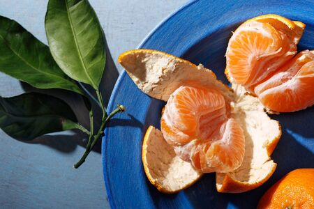 Fresh mandarin oranges fruit or tangerines with leaves on the table. Top view.