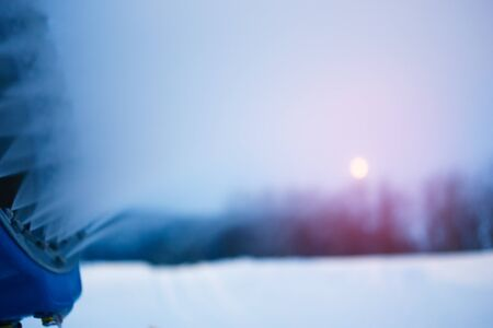Snow cannon in winter mountains. Snow-gun spraying artificial ice crystals. Machine making snow. Ski resort with snow.
