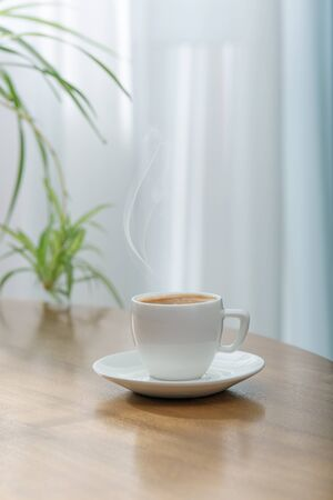 Fresh aromatic coffee in a white ceramic cup on a wooden table. Light background.