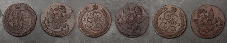 Numismatics. Old collectible coins made copper on a wooden table. Top view. Black backgraund. Banner.
