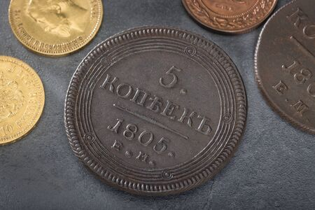 Numismatics. Old collectible coins made of silver, gold and copper on a wooden table. Top view.. Black backgraund.  Stock Photo