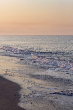 Sunrise, sunset at sea. Beautiful sky in the sun. Beautiful waves wash the sandy shore. Beautiful seascape