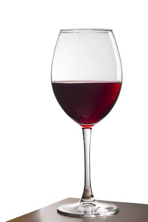 Glass of red wine on a wooden table. White background. Isolated white background.
