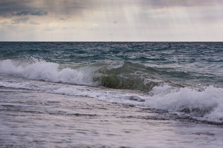 Seascape during storm and sunrise. Waves roll ashore against the backdrop of a beautiful sky with clouds and sunbeams.