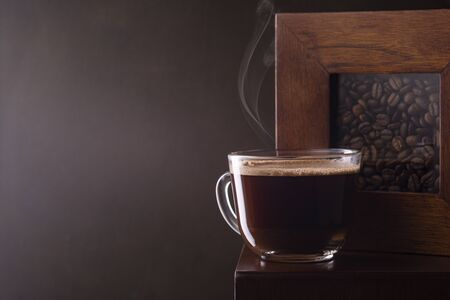Fresh aromatic coffee in a coffee cup and coffee beans on the table. Dark background. Banco de Imagens