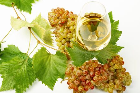 A glass of white wine, fresh grapes and grape leaves. White background.