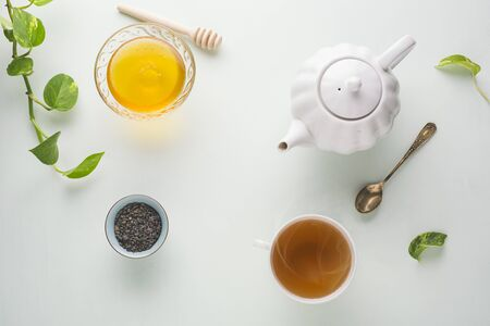Fresh brewed tea, teapot and honey on a light table. White dishes. light background. Top view.
