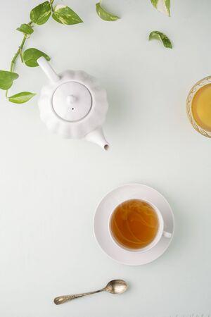 Fresh brewed tea, teapot and honey on a light table.