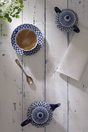 Kettle with fresh tea and a ceramic cup on the table